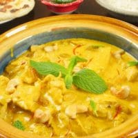 Chicken Korma ~ Instant Pot -- Cooked and dished out in a dark yellow ceramic bowl garnished with mint and served with fluffy basmati rice.
