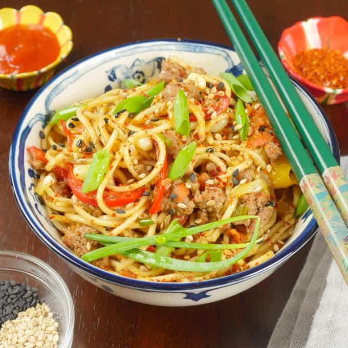 Cumin Lamb Indo-Chinese Noodles - Served in a blue and white Chinese rice bowl garnished with scallion greens and accompanied with a small dish of chili flakes. Served with chopstix.