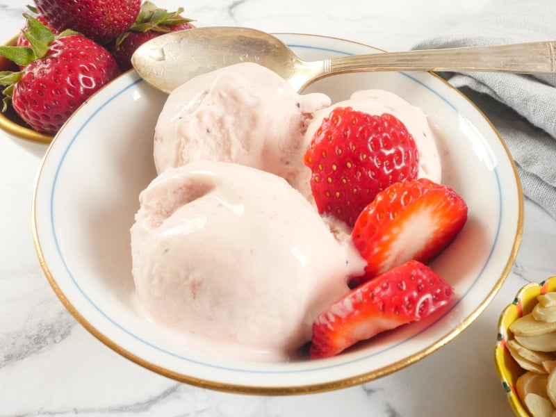 Roasted Strawberry Ice Cream (No Churn) Ice cream served up in a gold-rimmed bowl with some fresh strawberries for garnish, looking all creamy and beginning to melt.