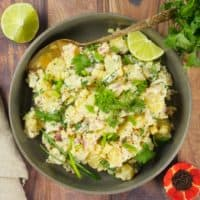 Indian-ish Yogurt Potato Salad - Served in a large grey bowl with a wedge of lime and a dusting of bright green chopped cilantro.
