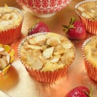 Cardamom Crunch Almond Cupcakes - Served on a gold platter with fluffy whipped cream and strawberries.