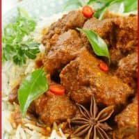 Instant Pot Beef Curry (Kerala) Rich Kerala beef stew on a bed of aged basmati rice and garnished with a sprig of curry leaves, slices of red chili, and a whole star anise.