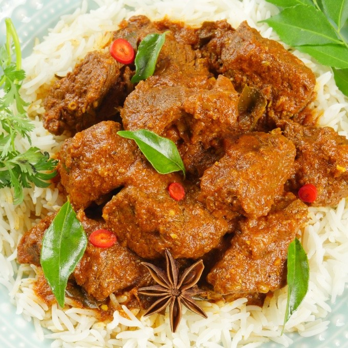 Rich Kerala beef stew on a bed of aged basmati rice and garnished with a sprig of curry leaves, slices of red chili, and a whole star anise.