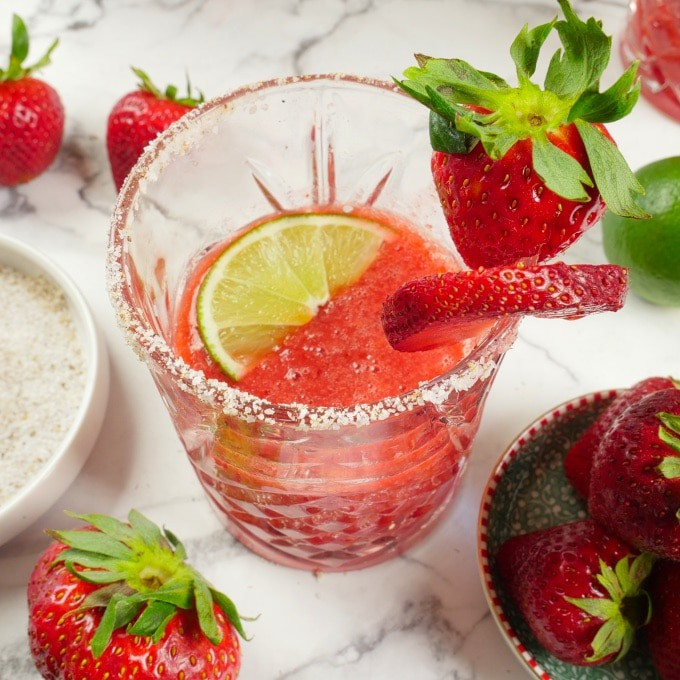 Roasted Strawberry Margarita Served garnished with extra strawberries, lime wedges, and a spicy salted rim.