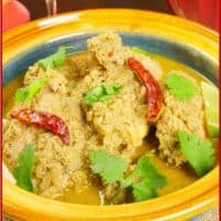 Served with a flutter of green cilantro and dried red chilies.