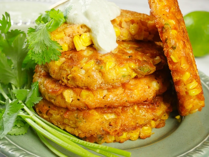 Sweet Corn Cakes - Stacked on a plate and garnished with minted yogurt, fresh cilantro, with a half a lime on the side.
