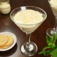 Easy Serradura (Sawdust Pudding) Layered puddings served with whole Marie biscuits and a small bouquet of mint.