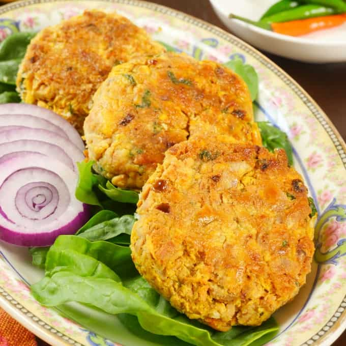 Fish Patties Goan-Style Served on a bed of greens and red onion slices.