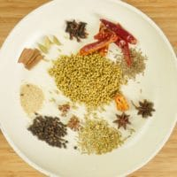 Whole spices in a large skillet ready for toasting.