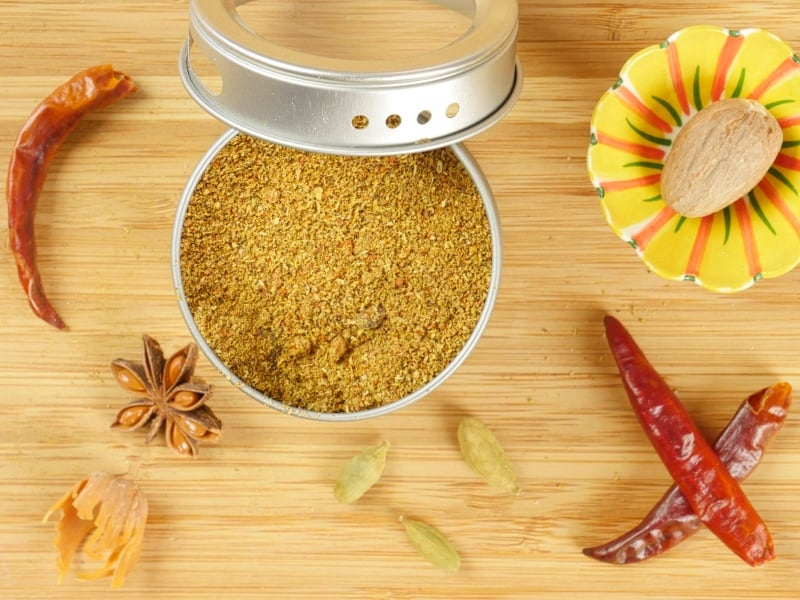 Goan Garam Masala - A spice tine filled with spice powder with whole spices keeping it company.