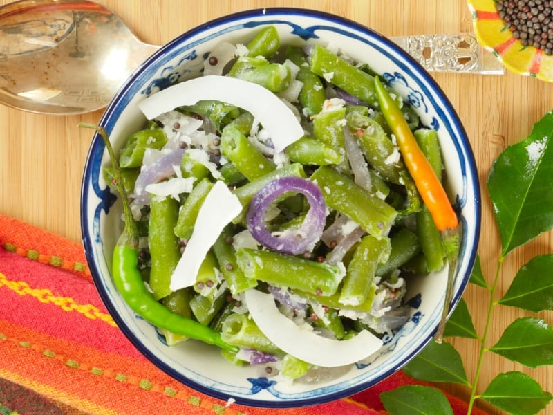 Easy Coconut Green Beans - Served in a blue and white bowl garnished with large coconut chips and orange green small chilies.