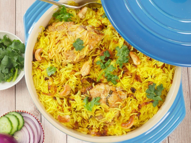 Goan Chicken Biryani has been cooked, garnished with toasted cashews, crispy brown onions, and a show of cilantro.
