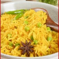 Spiced Rice (Goa) Served with a wooden spoon and garnished with whole spices, green peas, and fresh chilies.