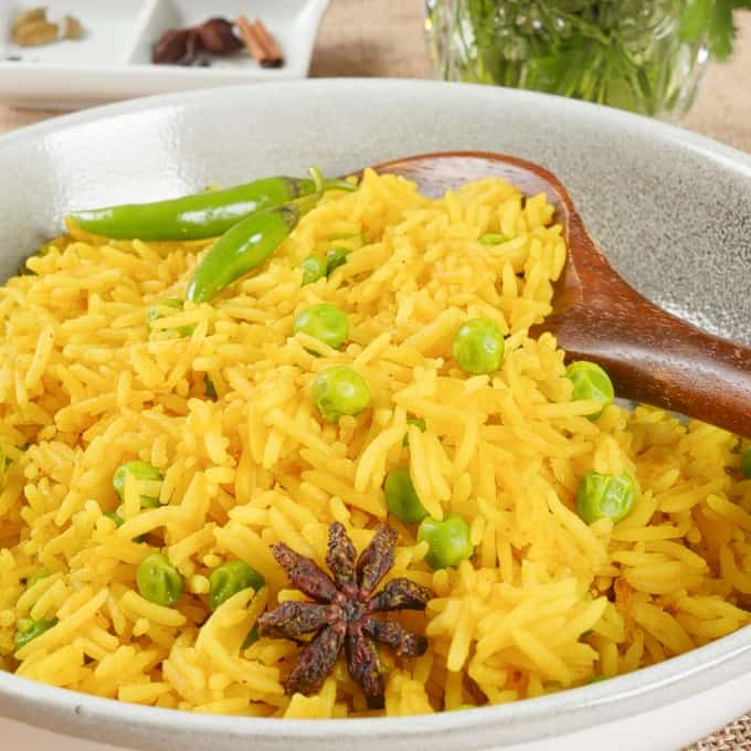 Served with a wooden spoon and garnished with whole spices, green peas, and fresh chilies.