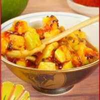 Instant Mango Pickle (miskut) - Served in a pretty gold-rimmed bowl with a wooden spoon.