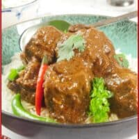 Red beef curry served on a bed of basmati rice with fresh chillies and a flutter of fresh cilantro leaves.
