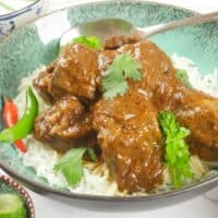 Red Beef Curry (Goan) Served on a bed of basmati rice with fresh chillies and a flutter of fresh cilantro leaves.