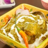 Comforting Chicken Saag Recipe ~ Served in a pretty square bowl garnished with drizzles of yogurt, an orange chili, and slices of shallot.