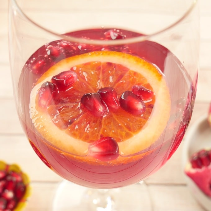Pomegranate Cocktail or Mocktail Served in a long-stemmed wine glass with pomegraniate arils and a blood orange slice.