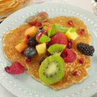 Three rice pancakes served with fruit salad and a flurry of mint leaves.