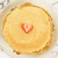 Rice Pancakes (Indian-style) A stack of rice pancakes ready for serving topped with some strawberry.