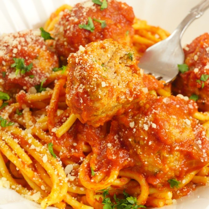 Spaghetti & Curry Meatballs ~ Sauced pasta topped with meatballs garnished with a dusting of parmesan and chopped cilantro.