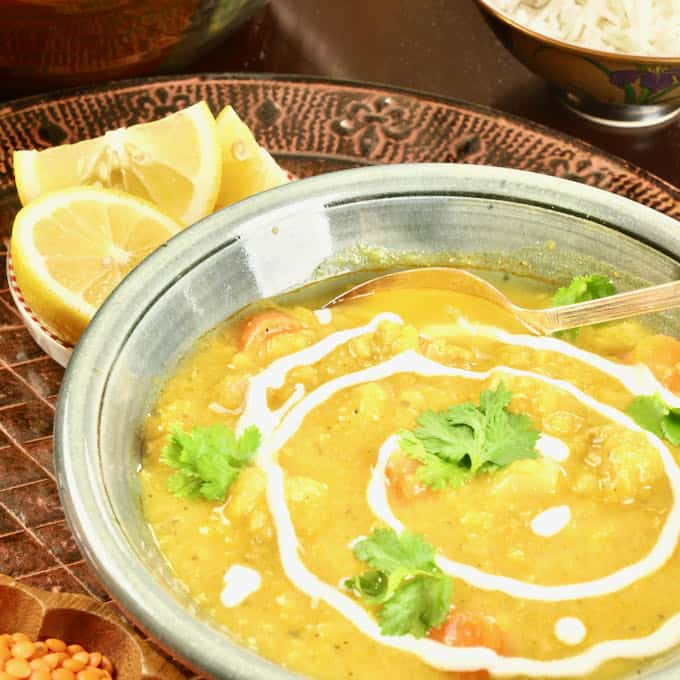 Glorious Chicken Mulligatawny Soup served with lemon slices, a bowl of rice, garnished with a drizzle of yogurt and a flutter of fresh cilantro.