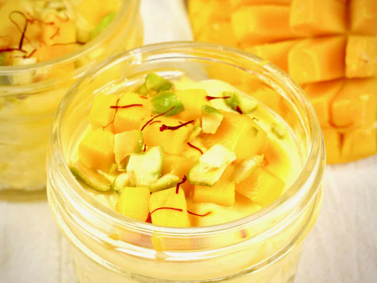 Mango fruit custard served in small jars garnished with chopped pistachios and saffron.