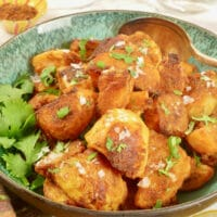Spiced Crunchy Roasted Potatoes Served in a dish and garnished with coarse salt and a flurry of chopped cilantro.