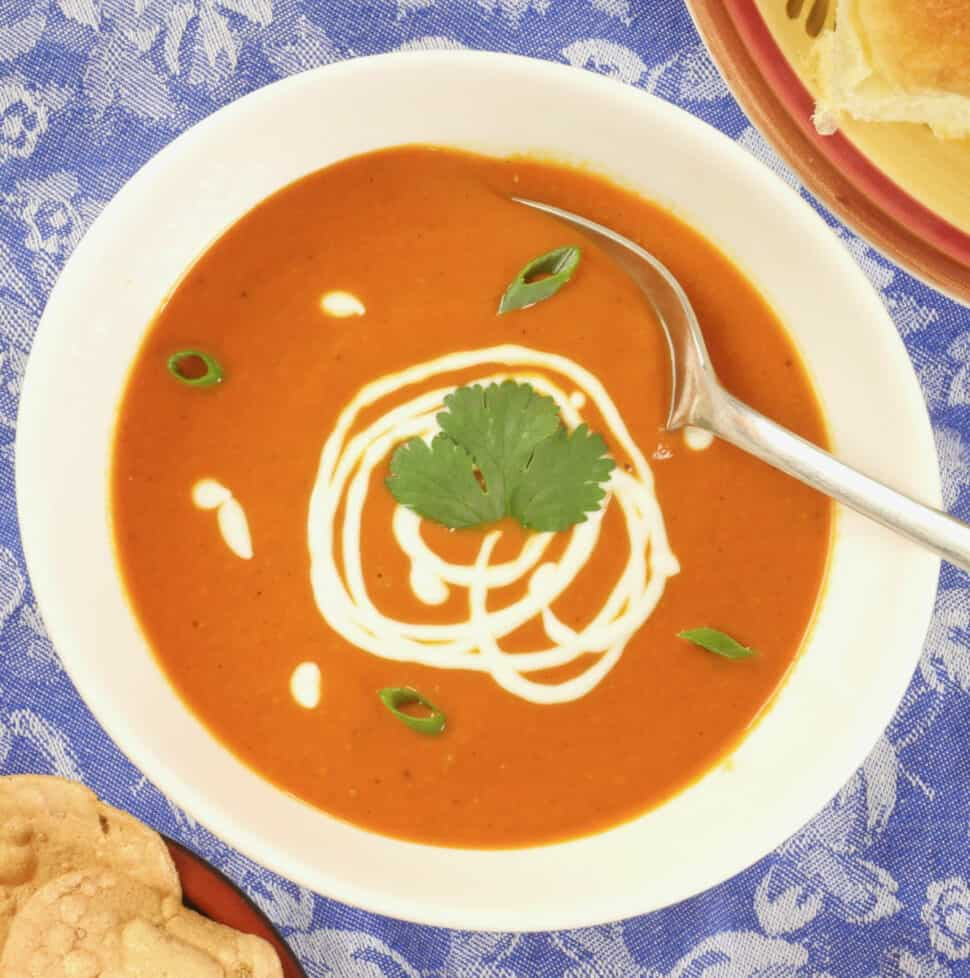 Indian Spiced Tomato Soup ~ Served in a scalloped white bowl, garnished with yogurt and a flurry of chopped cilantro.
