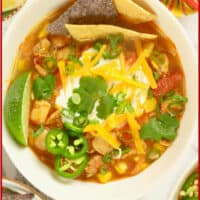 A chicken and white bean chili (stew) garnished with tortilla chips, yogurt, chopped scallions, shredded cheese and a flurry of cilantro leaves.