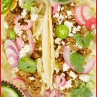 Taco Filling Ideas - Indianish Two tacos garnished pickled red onions, sliced radishes, cheese crumbles and a flutter of cilantro leaves.