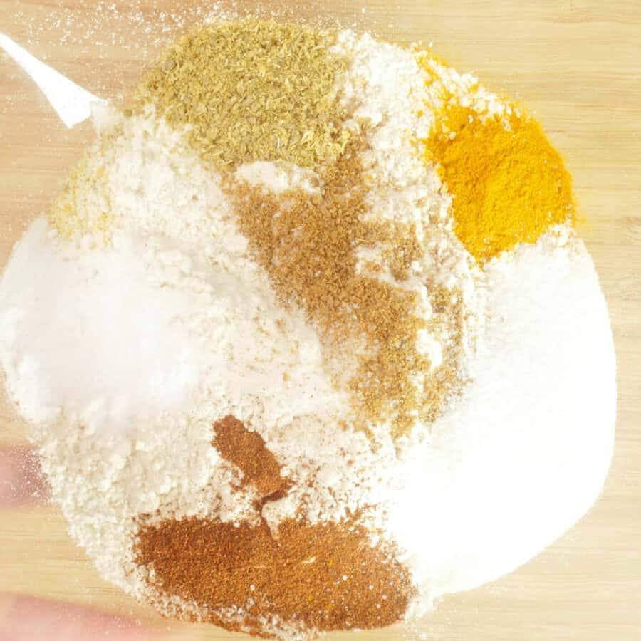 The flour, salt, soda, and spices in a bowl, ready for mixing together.