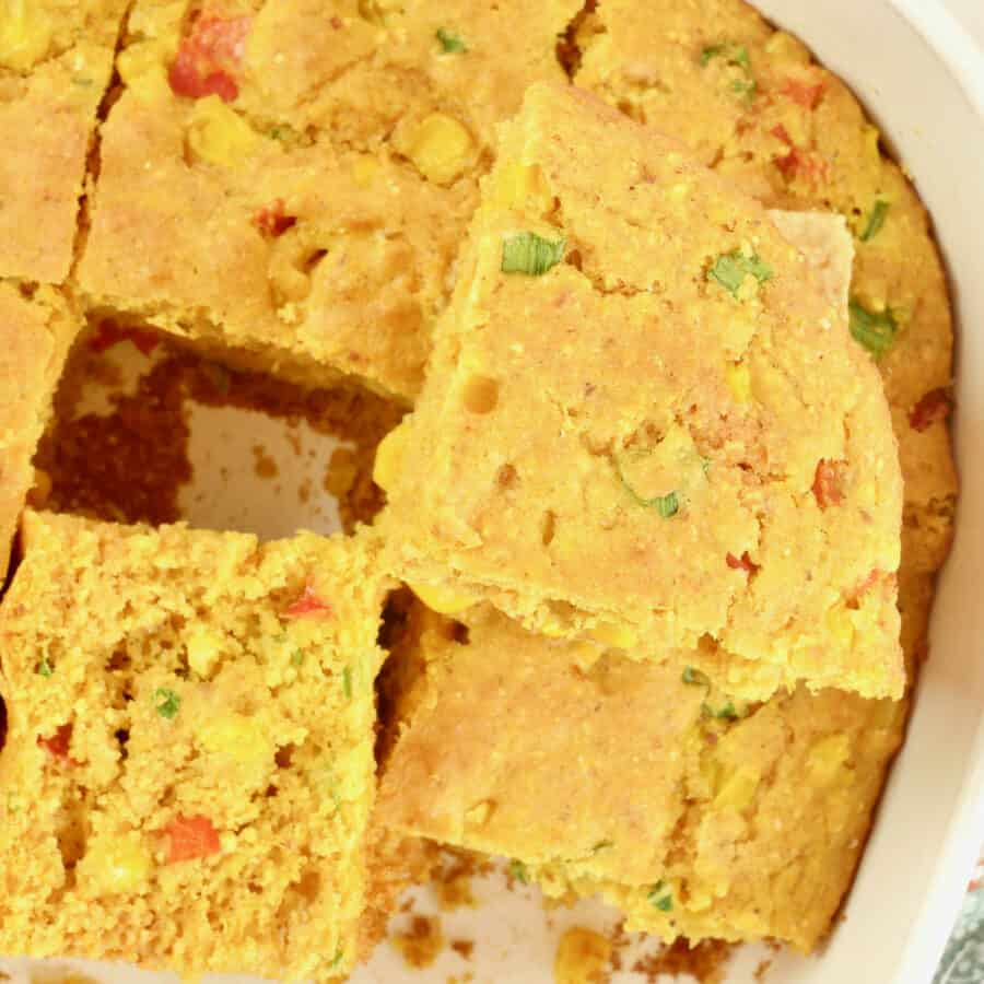 Cornbread baked in a square pan and the pieces cut to show the moist tender crumb.