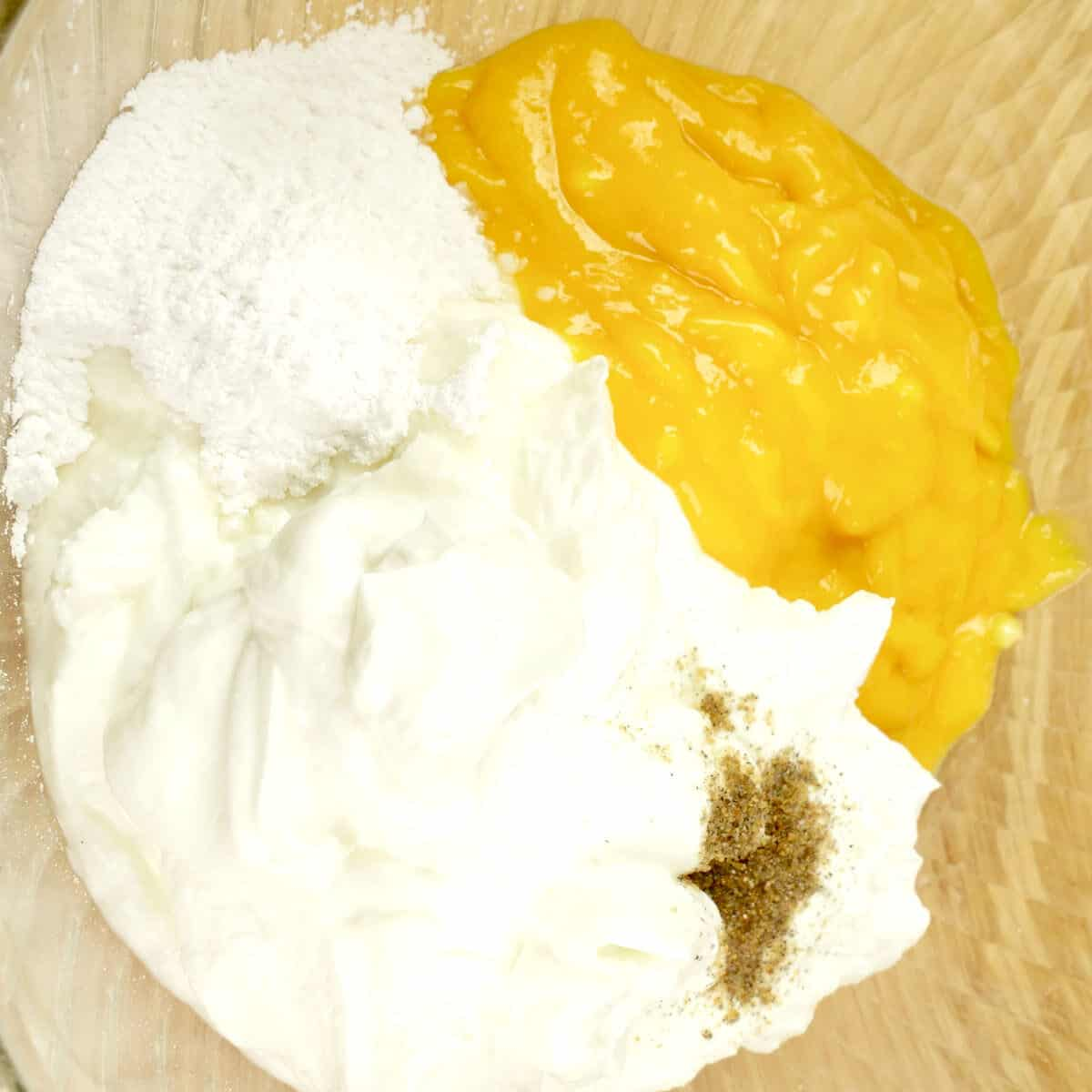 All the ingredients for mango fruit custard in a bowl, ready for mixing together.
