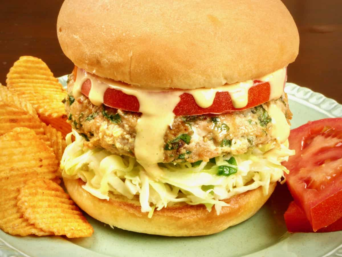 Burgers served on a bun with spicy potato chips, tomato, coleslaw and special sauce.