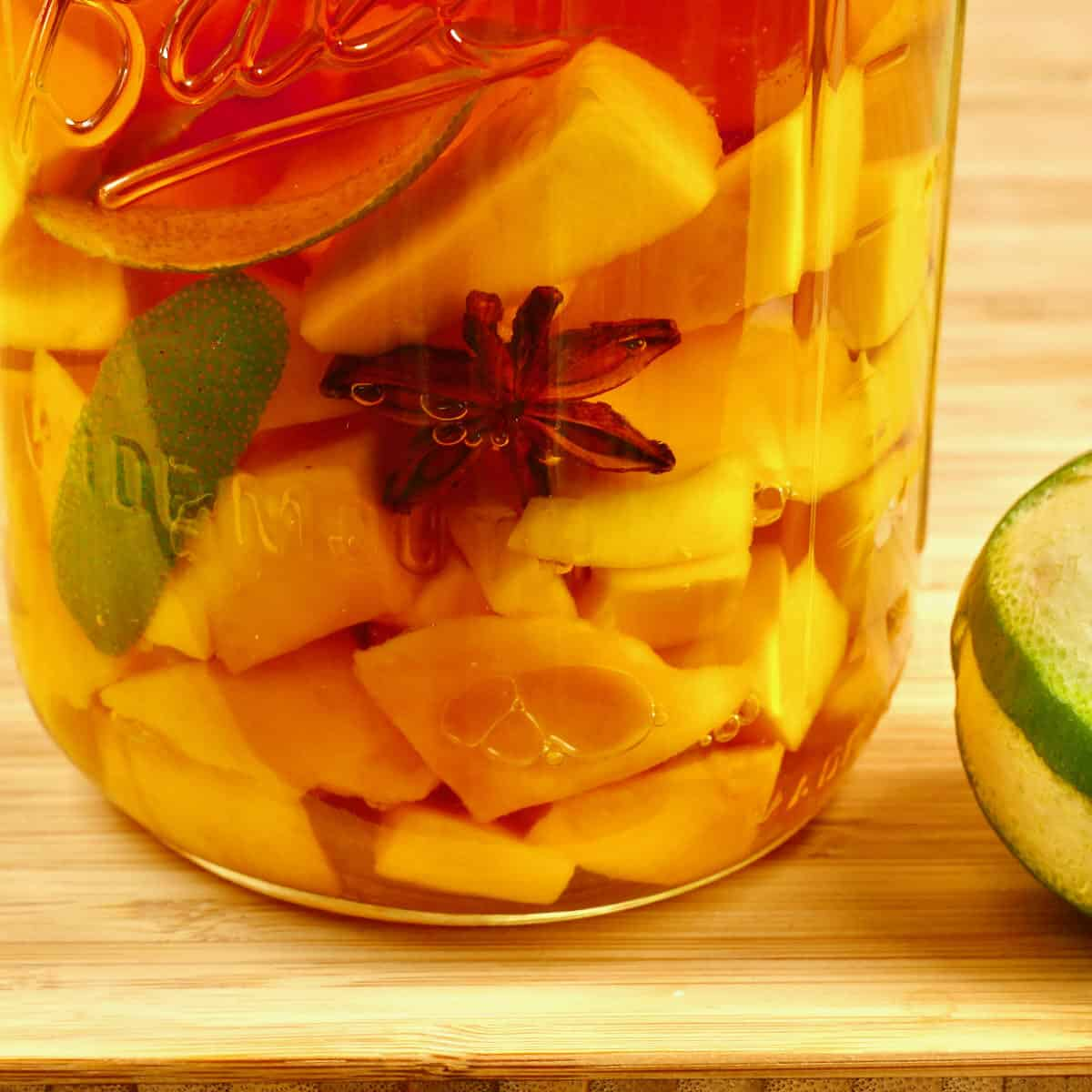 A quart canning jar with rum, lime peel, and mango pieces ready for steeping.