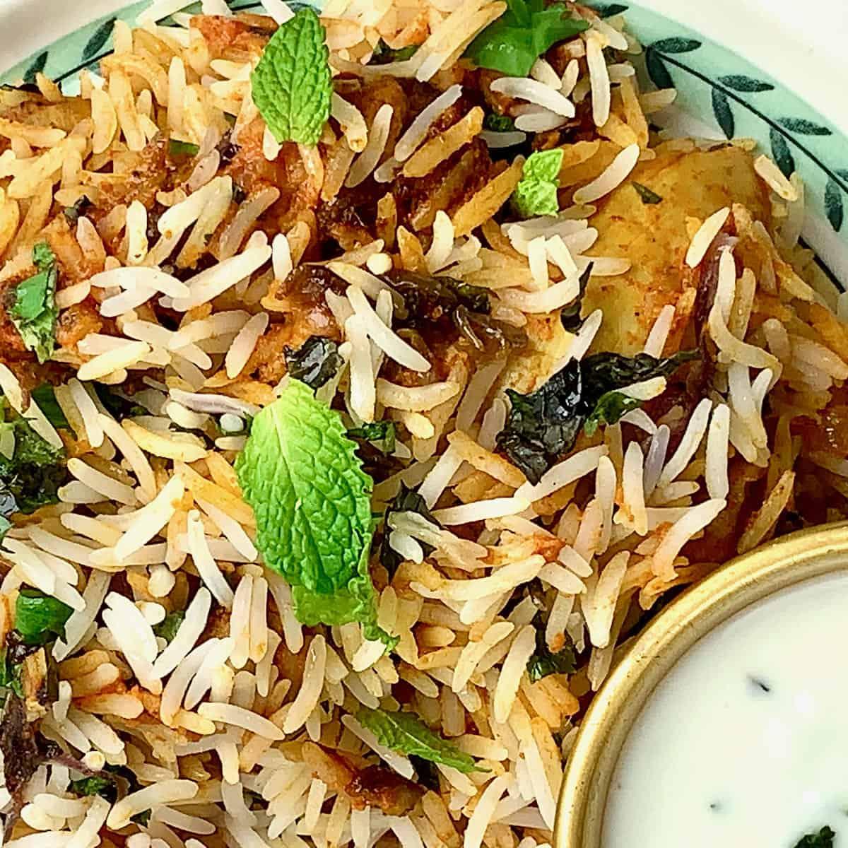 Tandoori Chicken Tikka Biryani served on a pretty plate with a flutter of fresh herbs and a side of raita.